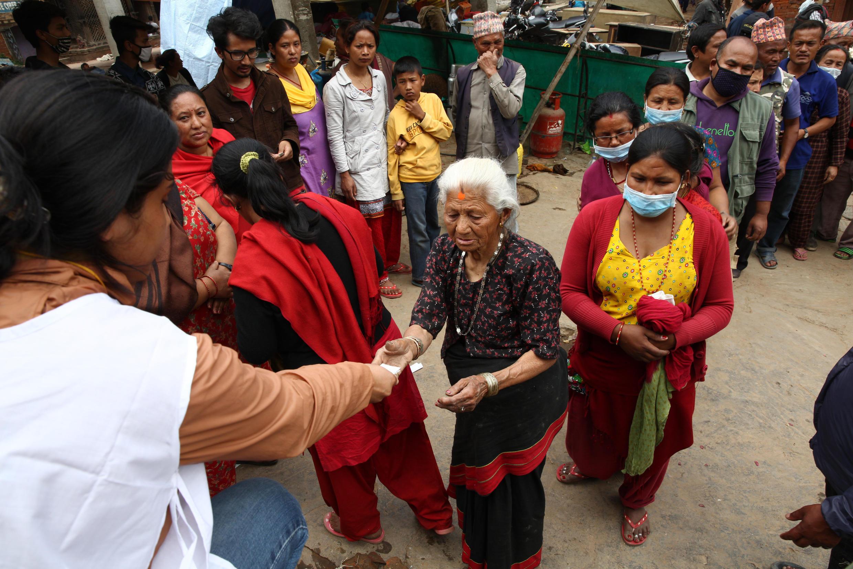 La Croix-Rouge et le Croissant-Rouge distribuent des tablettes purifiantes pour l'eau à Bhaktupur, à l'est de Katmandu, le 30 avril.
