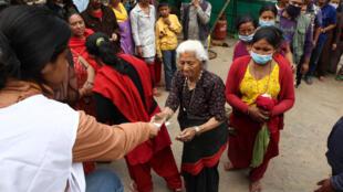 La Croix-Rouge et le Croissant-Rouge distribuent des tablettes purifiantes pour l'eau à Bhaktupur, à l'est de Katmandu, le 30 avril 2015.