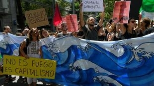 Des activistes du climat tiennent des pancartes sur lesquelles on peut lire: «Ce n'est pas un feu, c'est le capitalisme» «Bolsonaro est un criminel de l'environnement, un assassin» lors d'une manifestation à Barcelone le 23 août 2019.