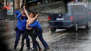 Militante do Femen protesta durante passagem do carro de Donald Trump nas comemorações pelo fim da Primeira Guerra Mundial