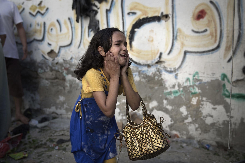Criança chora ao ver o local da explosão que matou pelo menos oito crianças e dois adultos no campo de refugiados de Shati, na zona norte da cidade de Gaza. 28 de julho de 2014