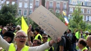"""Manifestante com cartaz """"Todos mentirosos"""" durante protesto na cidade de Amiens"""