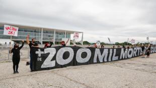 """Manifestantes sostienen una pancarta que dice """"Más de 200.000 muertos"""" durante una protesta contra el presidente Jair Bolsonaro y en honor a las doscientas mil personas muertas por la enfermedad del coronavirus, frente al Palacio Planalto en Brasilia, el 8 de enero de 2021"""
