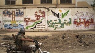Un soldat de l'ASL, le 9 mai 2013. Sur le mur, les graffitis signifient « la révolution est paisible » et « armée syrienne libre ».