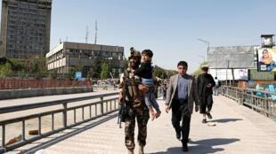 Un miembro de las fuerzas de seguridad afganas evacuando a un niño en el ministerio de la Comunicación, 20 de abril de 2019.