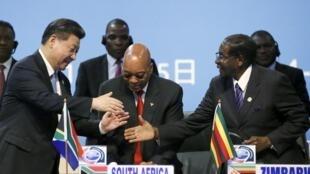 Le président chinois Xi Jingping salue ses homologues sud-africain, Jacob Zuma, et zimbabwéen, Robert Mugabe, lors du sommet Chine-Afrique à Johannesburg, le 4 décembre 2015.