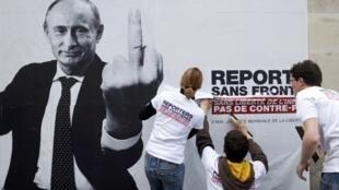 """Активисты """"Репортеров без границ"""" расклеивают плакаты с изображением В. Путина в связи с 20-м Днем свободы прессы в Париже 03/05/2013"""