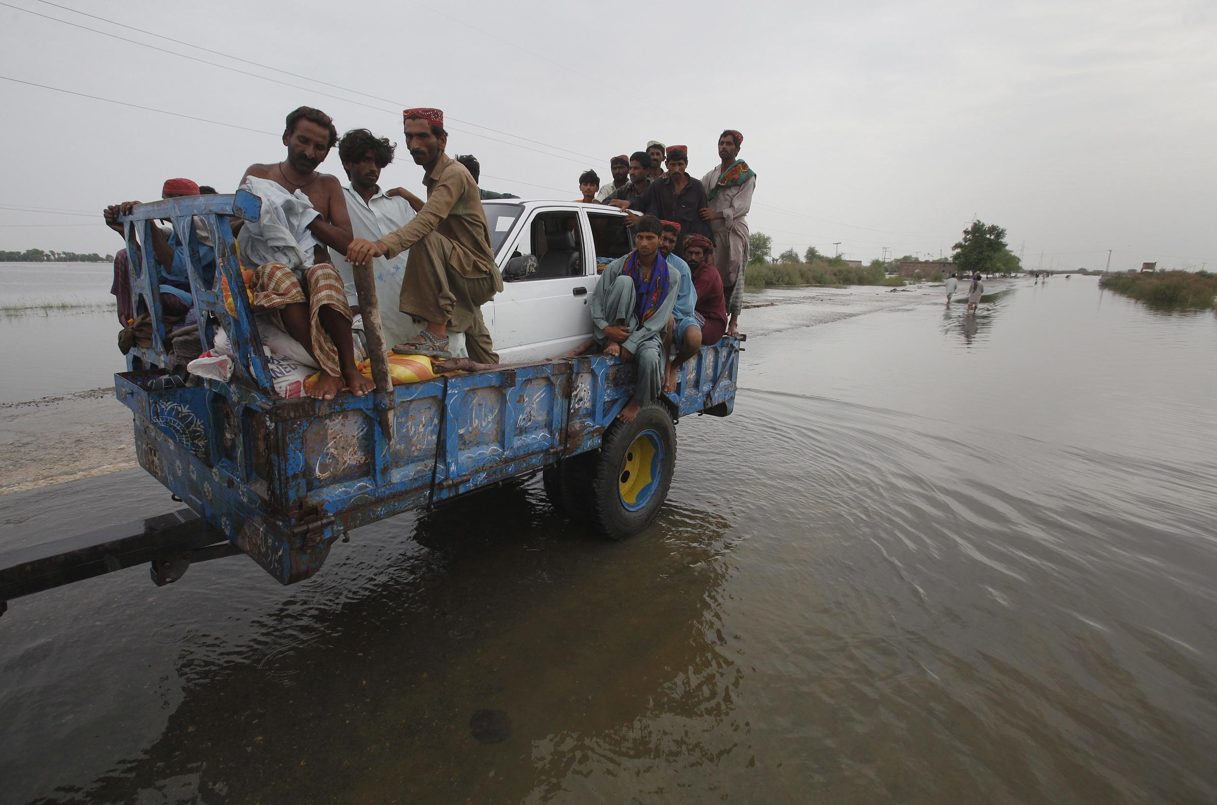 Villagers transporting a car after fleeing from flood water in Karampur