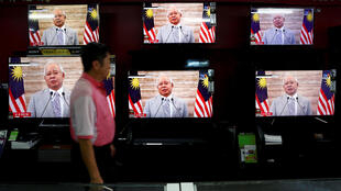 A man passes a live telecast of Malaysia's Prime Minister Najib Razak addressing the nation on the dissolution of Parliament at an electronics shop in Port Klang, Malaysia April 6, 2018.