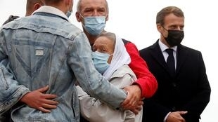 French President Emmanuel Macron (R) stands next to French aid worker Sophie Petronin (C) who is welcomed by her family after suspected jihadist hostage-takers freed the 75-year-old from nearly four years of captivity in Mali upon her arrival at the Villacoublay military airport near Paris on October 9, 2020. - Petronin was released along with a top Malian politician and two Italian hostages late on October 8, 2020. The last French citizen known to have been held hostage anywhere in the world since her abduction in 2016, a white-robed Petronin was embraced by her son as she touched down in Mali's capital, Bamako. (Photo by GONZALO FUENTES / POOL / AFP)
