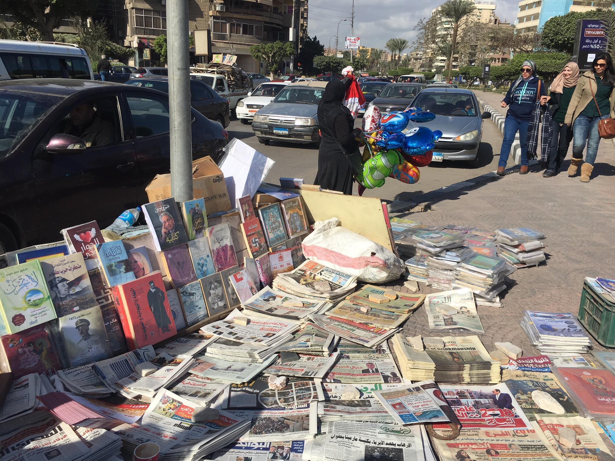Des étudiantes se dirigent vers une librairie à même le trottoir où les livres côtoient la presse et les magazines.