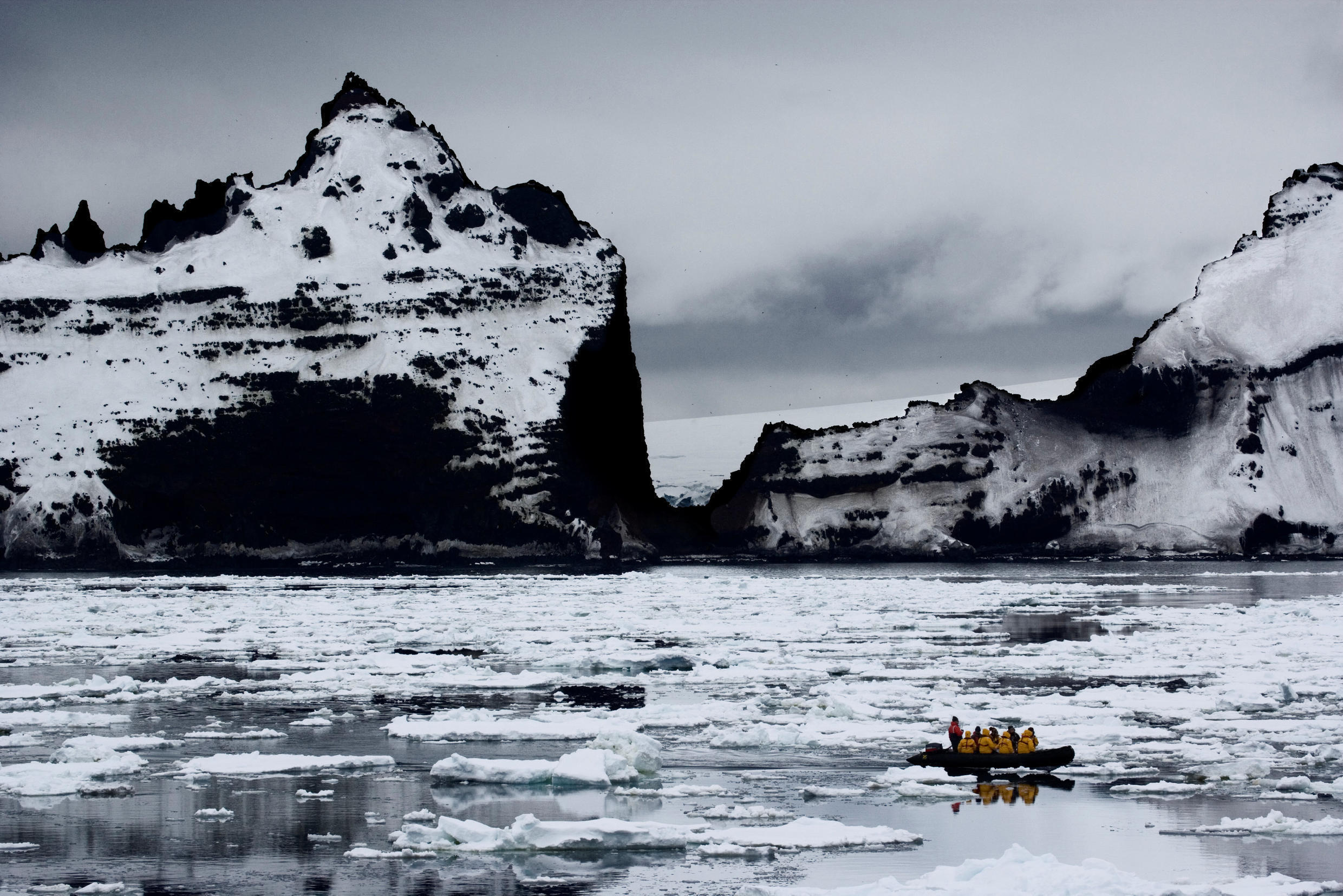 A boat passes a rocky cliff in Antarctica, home to the world's oldest ice.