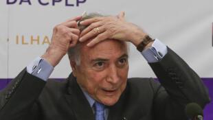 O Presidente do Brasil, Michel Temer, penteia-se durante a sessão de abertura Cimeira da CPLP