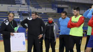 Le sélectionneur de l'équipe tunisienne, Sami Saidi (g), parle à ses joueurs durant un entraînement, à Hammamet, le 14 décembre 2021