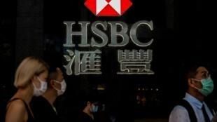Varias personas con mascarilla pasan frente a un logotipo del banco HSBC el 21 de septiembre de 2020 en Hong Kong