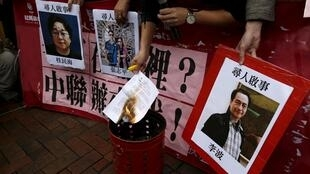 Một người biểu tình mang ảnh những người bị mất tích thuộc nhà xuất bản Mighty Current ở Hồng Kông