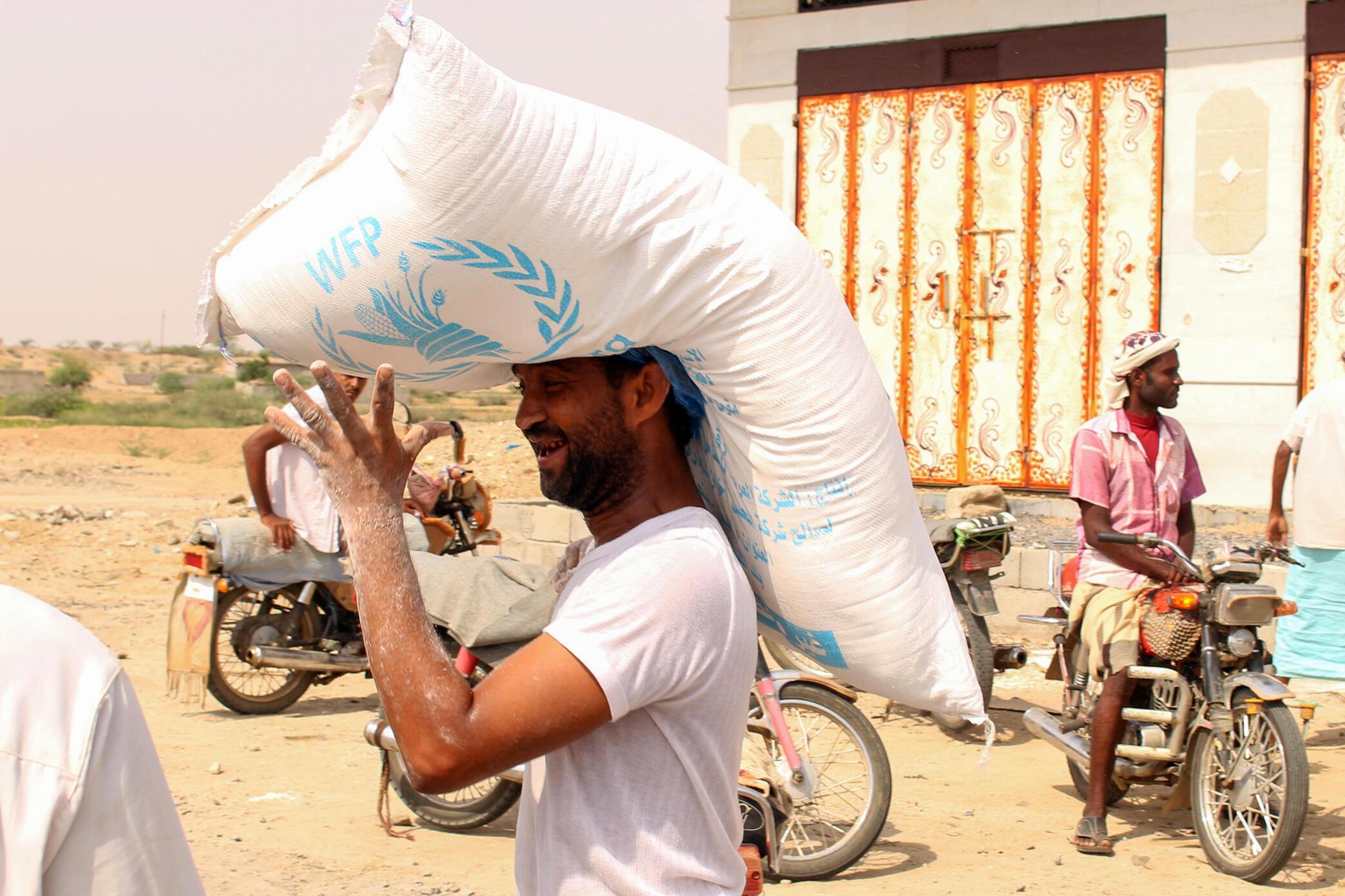 Homem carrega um saco com ajuda humanitária na região de Hajjah, no Iêmen, em julho de 2019.