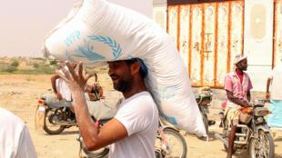 Un homme portant un sac d'aide alimentaire dans la région d'Hajjah au Yémen en juillet 2019 (image d'illustration).