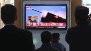 Passageiros em uma estação de trem assistem a uma reportagem sobre exercícios de tiros da Coreia do Norte. 31 de março de 2014.