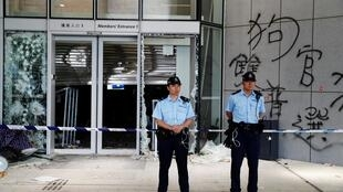 Policemen stand in front of graffiti on the walls of the Legislative Council, a day after protesters broke into the building in Hong Kong, China July 2, 2019.