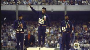 Lee Evans (c), Larry James (g) et Ronald Freeman (d) en bérets noirs sur le podium du 400 m.