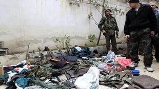 A Syrian soldier displays weapons seized from what officials say were gunmen, during the tour of Arab monitors in Damascus countryside Harasta January 26, 2012.