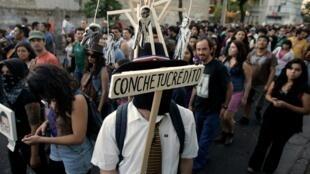 Estudante carrega na cabeça foto do presidente chileno Sebastián Piñera, em marcha pela educação.