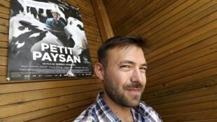 Hubert Charruel pose avec l'affiche de son premier film, « Petit paysan ».