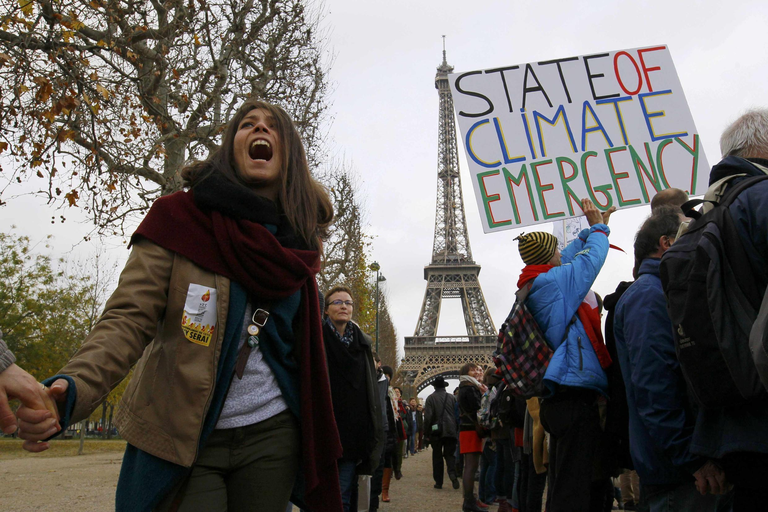 Environmentalists hold hands as they form a human chain during a demonstration near the Eiffel Tower in Paris, France, as the World Climate Change Conference 2015 (COP21) continues near the French capital in Le Bourget, December 12, 2015.