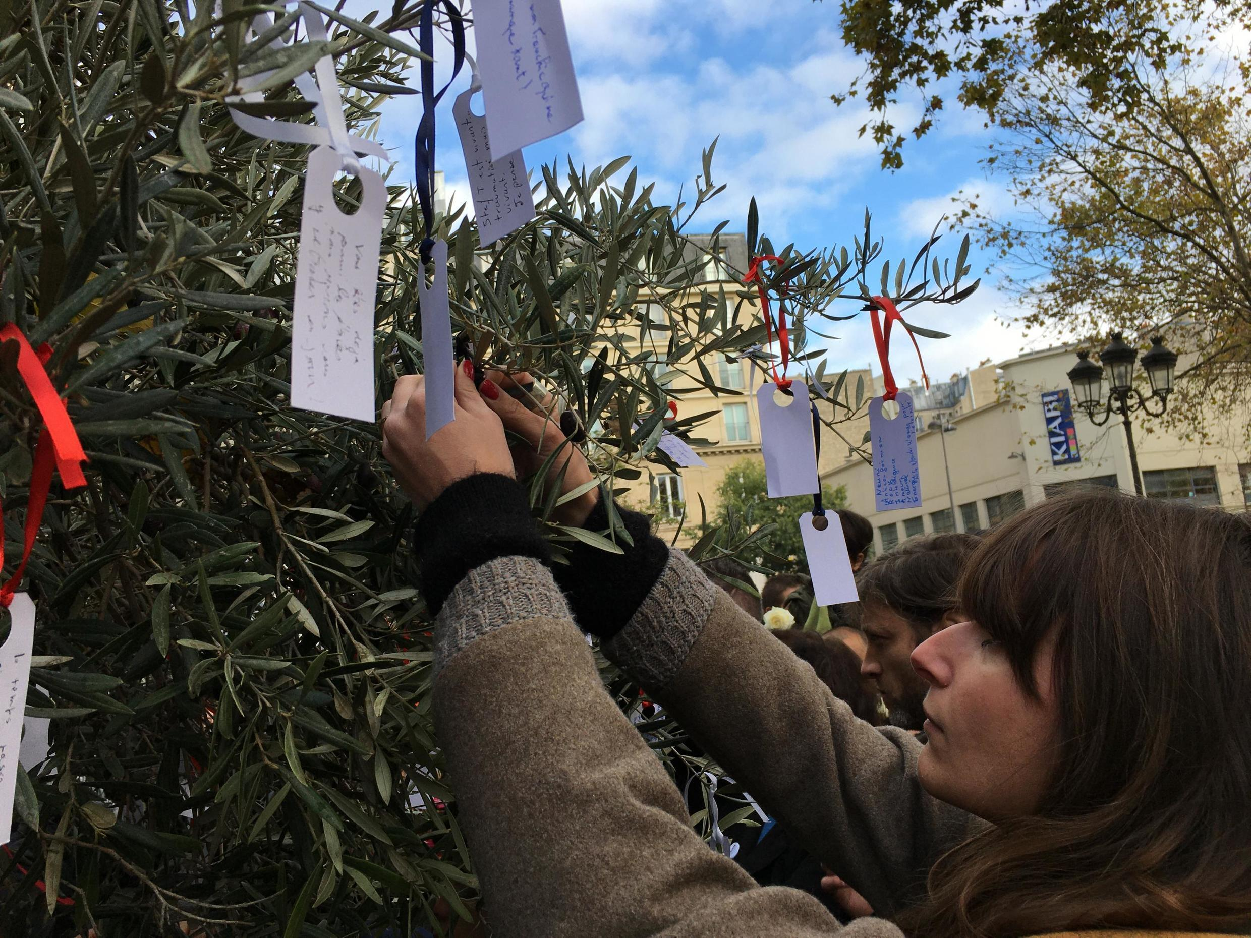Survivors and families of victims of terror attacks in the Paris region pin messages to an olive tree at a fourth anniversary ceremony, 13 November 2019.