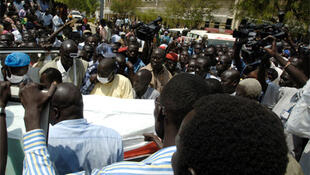 Crowds watch as the bodies of Jimmy Lemi Milla and his bodyguard are carried out of the Ministry of Rural Development.