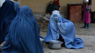 Sur cette photographie prise le 7 juin 2017, des femmes afghanes attendent avec leurs enfants de recevoir de la nourriture donnée par une organisation caritative privée pendant le mois sacré du ramadan, à Jalalabad.