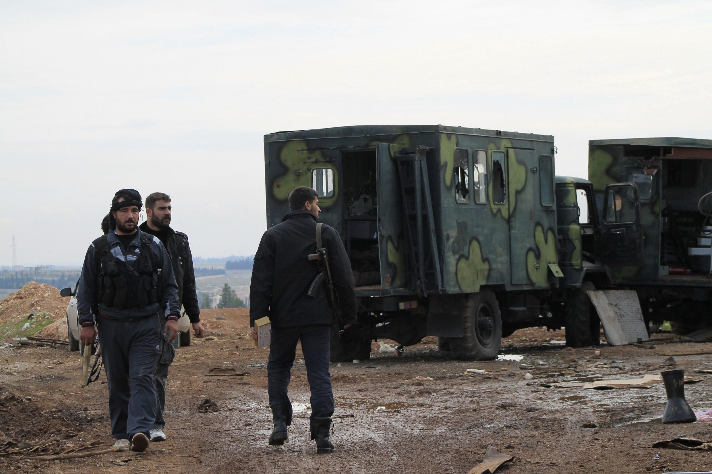 Free Syrian Army fighters near military trucks after they said they fought and defeated government troops at a military base at the town of Atareb near Aleppo