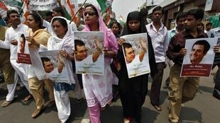 Activists from the youth wing of Congress hold portraits of Rahul Gandhi, a lawmaker and the son of India's ruling Congress party chief Sonia Gandhi, during a protest march against his arrest in Kolkata May 12, 2011.