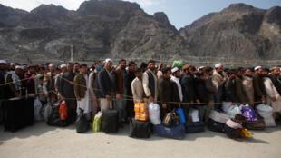 Cidadãos afegãos esperam para atravessar a linha no posto fronteiriço de Torkham, no Paquistão