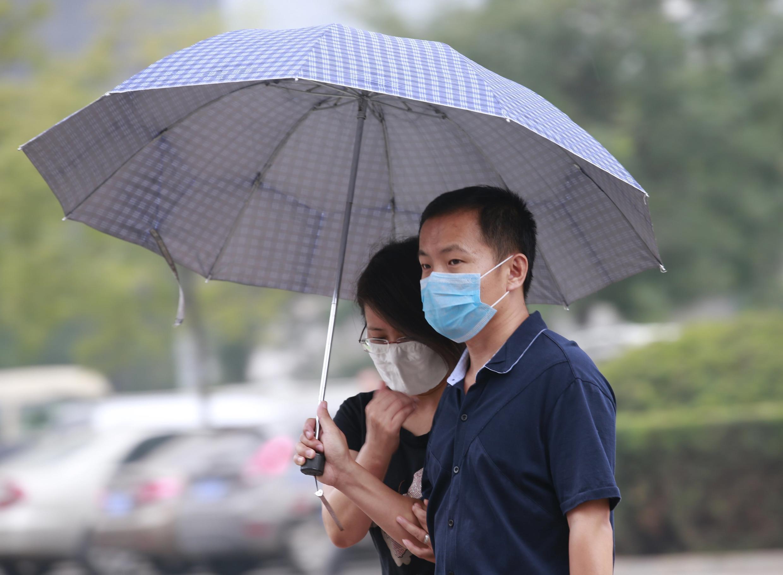 Una pareja se protege de la contaminación y la lluvia, distrito de Binhai, Tianjin, 18 de agosto de 2015.