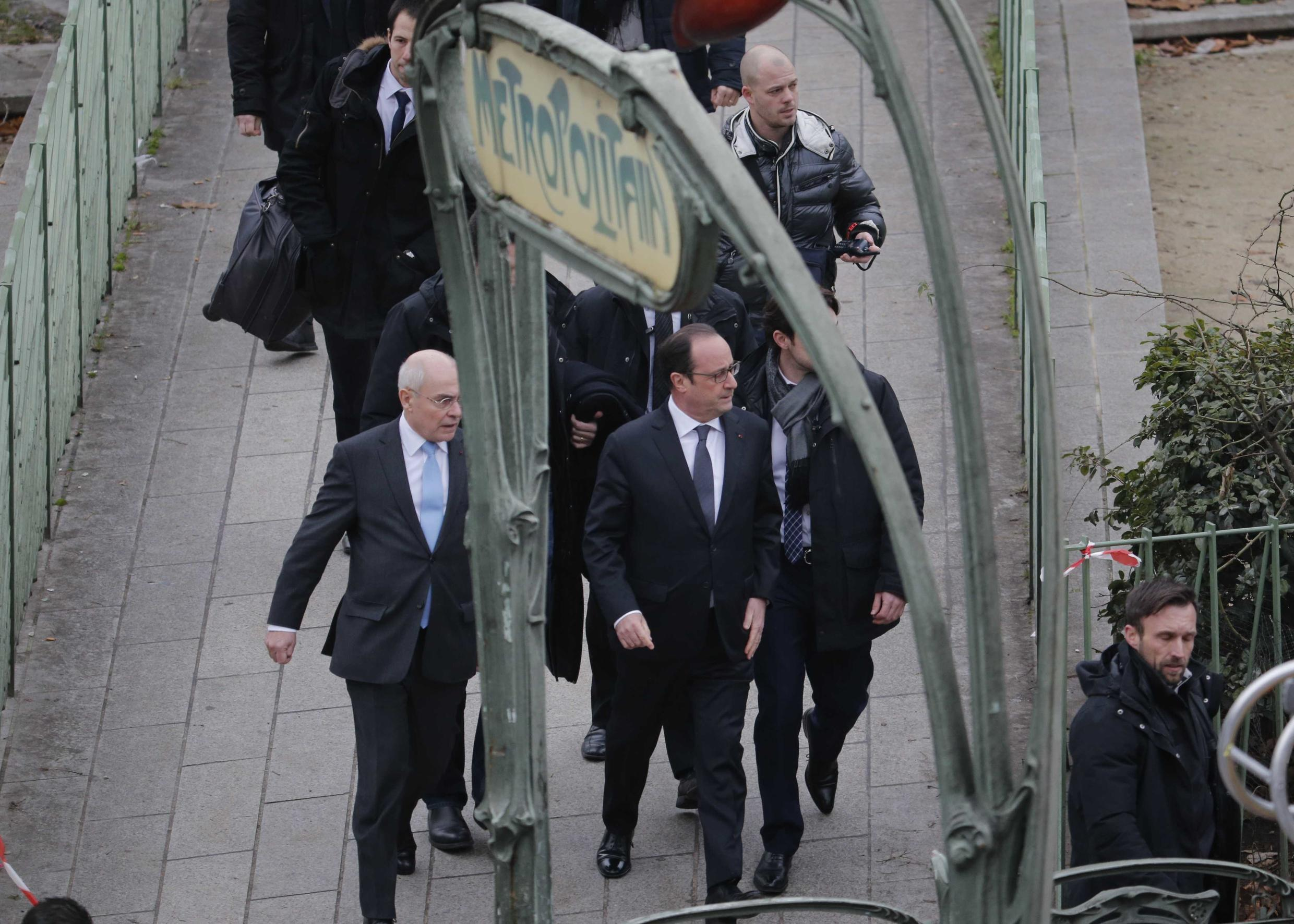 French President François Hollande (C) arrives at the scene of the attack on Charlie Hebdo's offices