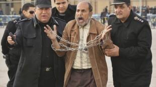 Le Caire, 19 janvier 2012. Des policiers tentent de calmer un manifestant anti-Moubarak devant l'Académie de police où se tient le procès de l'ancien président égyptien.