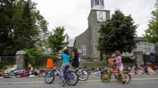 Niños residentes de Kahnawake, Quebec, observan cientos de zapatos infantiles colocados frente a la Iglesia de San Francisco Javier, donde la comunidad Mohawk Kahnawake, Quebec, se conmovió por el hallazgo de una fosa común de 215 niños indígenas en la Escuela Residencial Kamloops en Columbia Británica