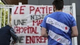 "An ER staffer in front of the gates of a Paris public hospital, wearing a message that says ""on strike"""