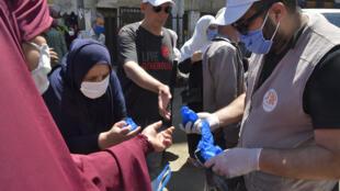 Des Algériens reçoivent des masques dans la banlieue d'Alger le 21 mai 2020.