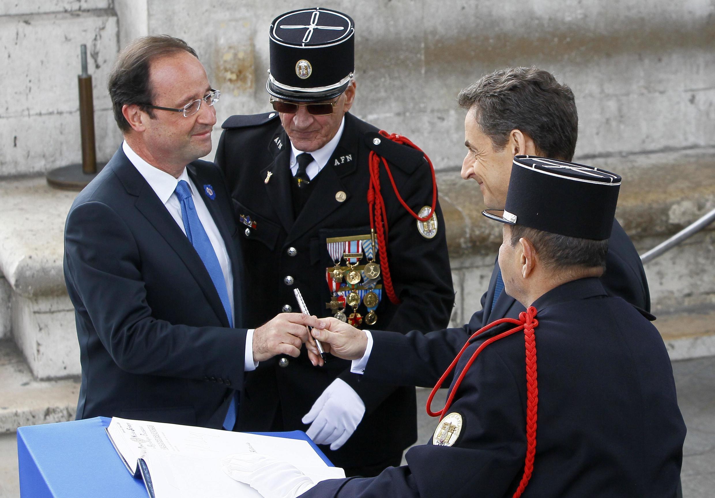 Hollande (esq.) e Sarkozy participaram lado a lado de homenagens a soldados franceses mortos na Segunda Guerra Mundial.