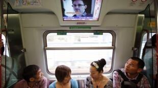 Экран в вагоне электрички Гон-Конга, на котором транслируется новостная лента с изображением Сноудена (архив)