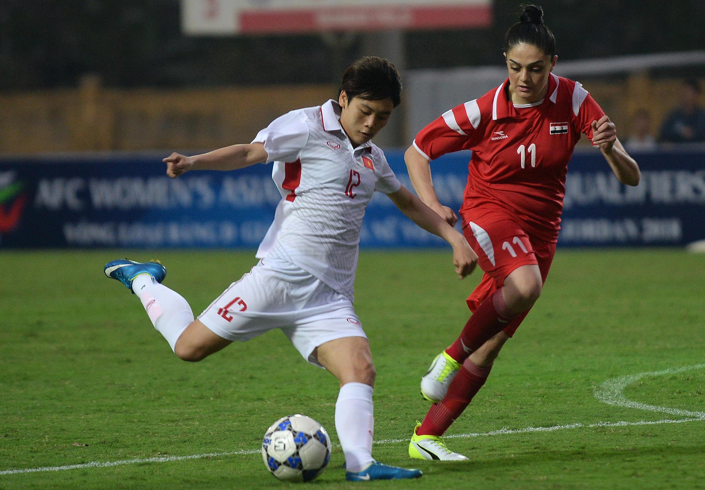 Nữ tuyển thủ Việt Nam Hải Yến (áo trắng) trong pha tranh bóng với cầu thủ Nancy Muammar của Syria trong trận vòng loại Asian Cup 2018 tại Hà Nội ngày 05/04.