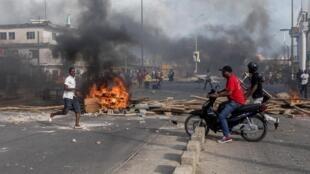 De jeunes manifestants ont dressé des barricades faites de pneus en feu ou de planches de bois dans le quartier de Cadjehoun, où se situe la résidence de l'ancien président Boni Yayi (2006-2016), à Cotonou, le 1er mai 2019.