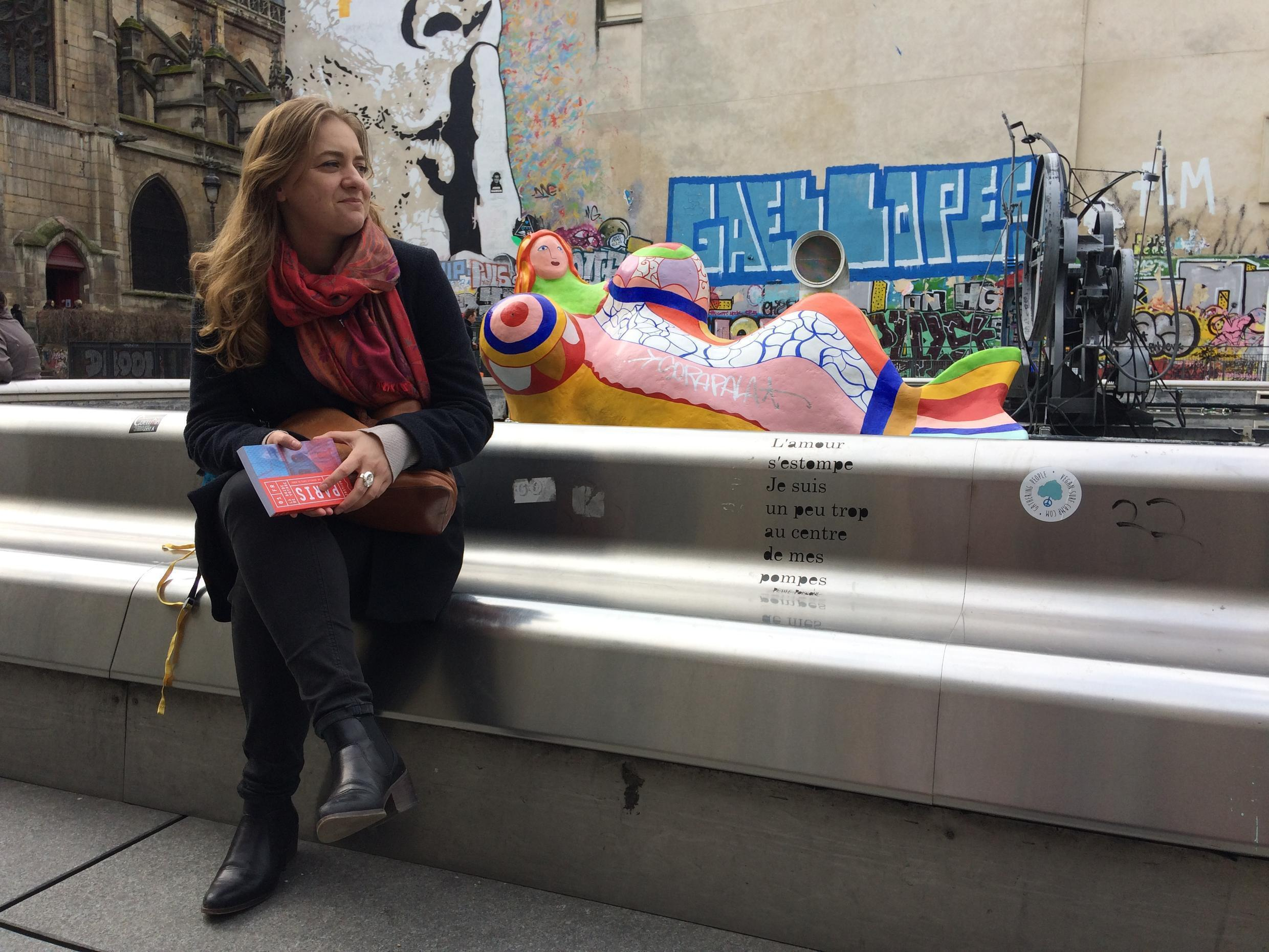 Charlotte Soulary, author of the Guide de Voyage Paris in front of one of Nikki Saint Phall's celebratory sculptures
