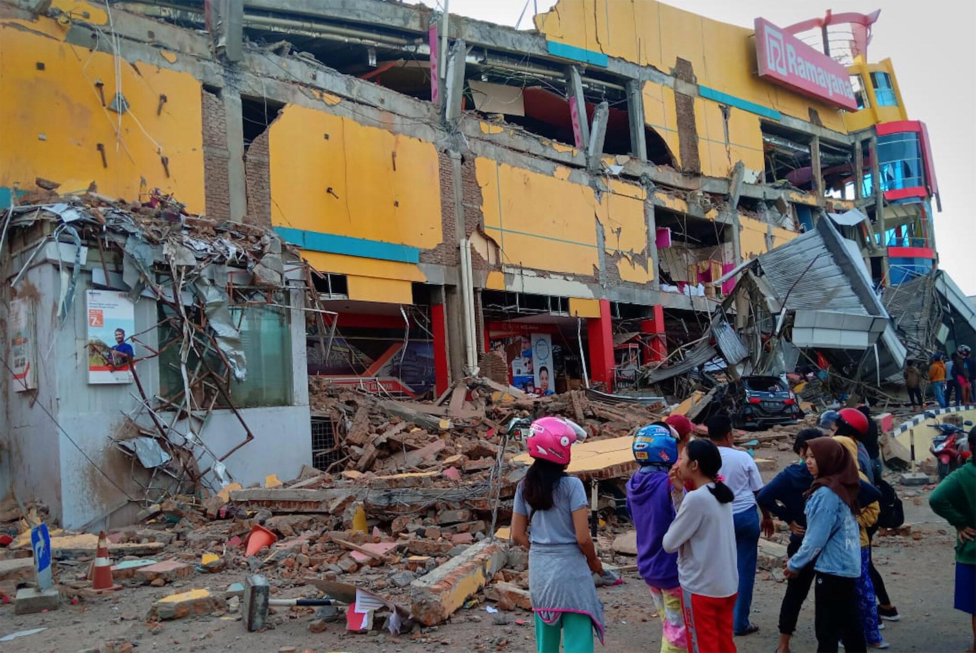 Habitantes de Palu observan los daños causados por el tsunami en un centro comercial, el 29 de septiembre, 2018.