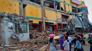 Palu residents look at the damage