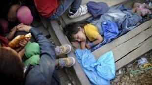 Menina síria dorme ao lado de um grupo de mais de mil migrantes na Macedônia.