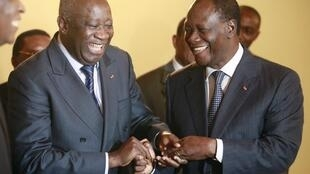 Laurent Gbagbo and Alassane Ouattara laughing during a meeting in Abidjan on 27 November
